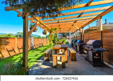 Barbecue and picnic area of hotel with row of tables and grills under the shed