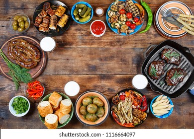 Barbecue picnic in honor of Memorial Day in the United States or lunch weekend in the open air. Fried steaks, grilled vegetables, potatoes, corn, sauces and beer
