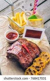 Barbecue pork ribs, corn, fries and lemonade on craft paper