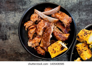 Barbecue pork ribs with grilled sweetcorn.  Top view on black plates over slate.  Sticky sauce.