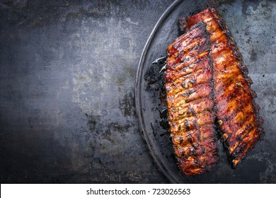 Barbecue pork spare ribs as top view on an old rustic board