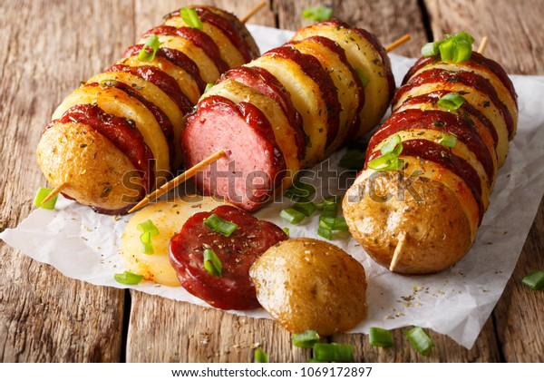 brochettes de pommes de terre au barbecue avec saucisse salami et oignon vert en gros plan sur la table. horizontal