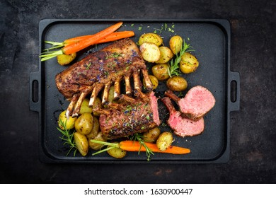 Barbecue rack of lamb with carrot and potatoes offered as top view on a modern design cast iron tray with copy space