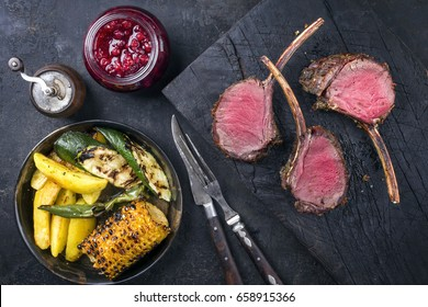 Barbecue Rack of Venison with Potatoes and Vegetable as top view on an old burnt wooden board