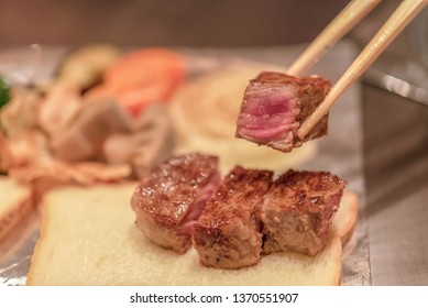 Barbecue rib eye steak, Selected focus on a dry aged Wagyu steak on chopsticks.