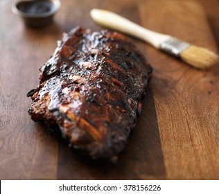 barbecue ribs with sauce brush on wooden surface
