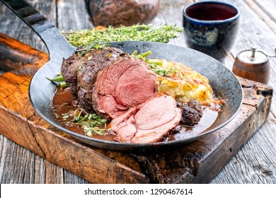 Barbecue roast boar joint with roesti and game red wine sauce as top view in a wrought-iron pan