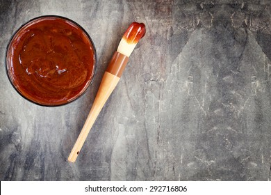 Barbecue sauce with basting brush over stone table with room for copy space.