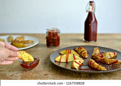 Barbecue sauce bottle and jar and potato wedges plate on wooden table, with woman hand.