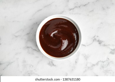 Barbecue sauce in bowl on marble background, top view