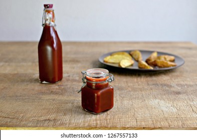 Barbecue sauce jar and bottle and potato wedges on wooden table
