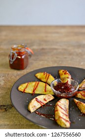 Barbecue sauce jar and potato wedges on wooden table