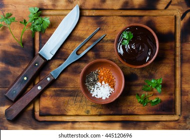 Barbecue sauce, salt, red and black pepper in clay bowls, meat fork, knife and napkin on wooden cutting board. Top view.