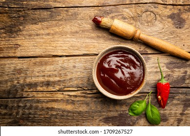 Barbecue sauce in a saucer with basting brush over rustic barn wood table, top view with copy space.