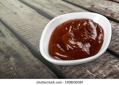 Barbecue sauce in a white ceramic saucer on a wood table.
