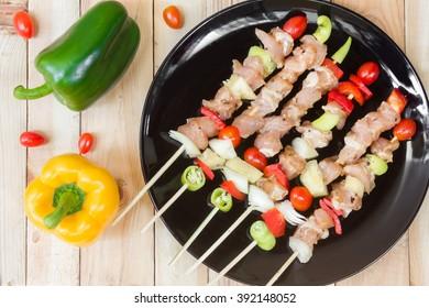 Barbecue seasoned meat with vegetables on skewers.