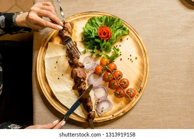 Barbecue skewers with juicy meat  on plate, vegetables on the board