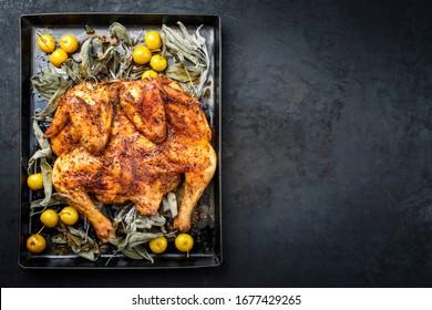 Grillis de poulet al mattone à base de barbecue avec mini pommes et feuilles de sauge en vue de dessus sur un vieux plateau de métal avec espace de copie