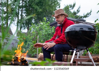 Barbecue time. European man in hat waiting for grilled food. He is sitting near fire and rest.