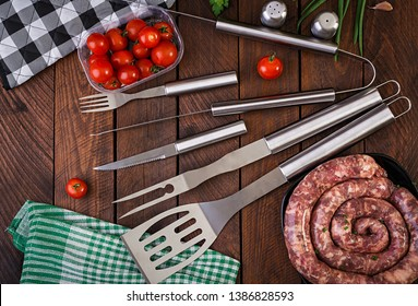 Barbecue Tools and sausage on wooden table. Flat lay, top view