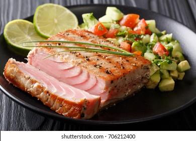 Barbecue tuna steak with lime and avocado cucumber salsa closeup on a plate. horizontal