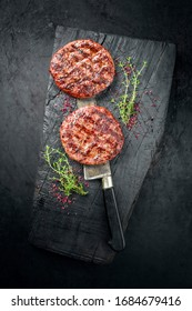 Barbecue Wagyu Hamburger with red wine salt and herbs as top view on a charred wooden board