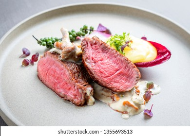 Barbecue wagyu point steak from beef sliced with chanterelle in sauce and mashed potatoes as top view on a modern design plate