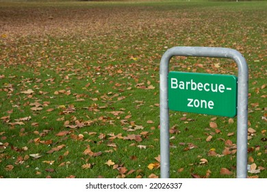 Barbecue zone sign with a meadow covered with autumn leaves in the background