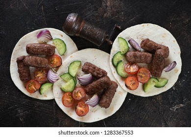 Barbecued balkan cevapcici sausages with vegetables on tortilla wraps, flatlay on a dark brown stone background