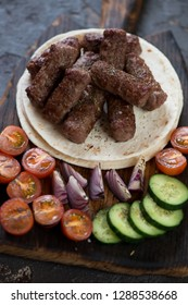 Barbecued cevapcici or skinless beef sausages with tortilla wraps and vegetables, vertical shot