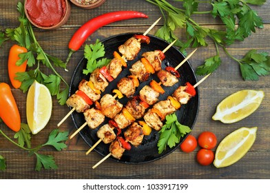 Barbecued chicken kebab with bell pepper in frying pan, vegetables and herbs on wooden table, top view.