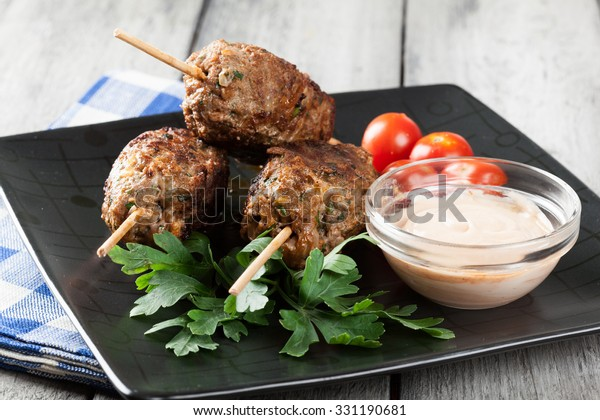 Barbecued kofta with vegetables on a plate. Selective focus