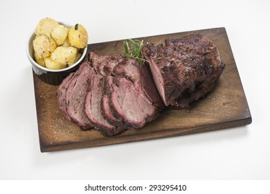 Barbecued lamb chops on a plank served with potatoes