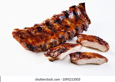 Barbecued and marinated sticky spare ribs on a white background with copy space.