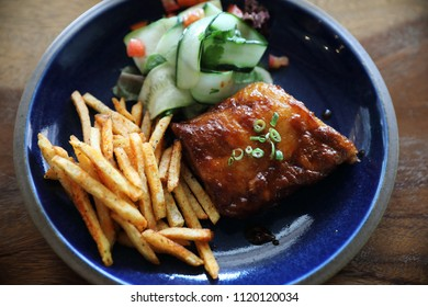 barbecued pork ribs steak with fresh vegetables on an old rustic wooden in restaurant
