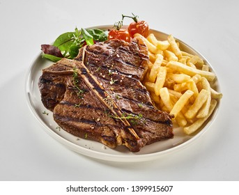 Barbecued T-bone steak with pommes de frites and fresh greens seasoned with herbs and served on a plate over white for menu advertising