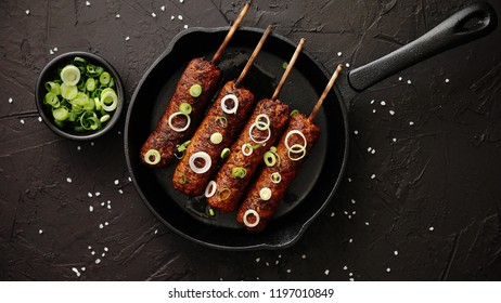Barbecued turkey kebab decorated with fresh onion and chive in frying pan, top view. Black stone background.