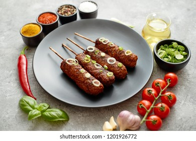 Barbecued turkey kebab decorated with fresh onion and chive black plate, top view. Dark stone background.