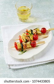 Barbecued Vegetable and Turkey Kebabs. Shashlik with turkey, cherry tomatoes, zucchini, onion, red pepper and fresh rosemary. Concept for a tasty and hearty dish. Bright wooden background. Copy space