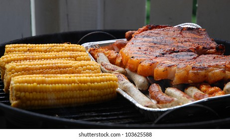 Barbecuing corn, pork chops and bratwurst sausages