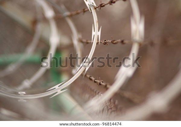 Barbed and razor wire on a fence.