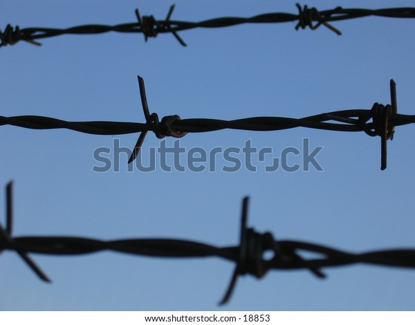 Barbed wire against a blue sky.