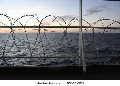 Barbed wire attached to the ship hull, superstructure and railings to protect the crew against piracy attack in the Gulf of Guinea in West Africa sailing during sunset.