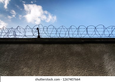 Barbed wire fence around prison walls, blue cloudy sky in background, security, crime or illegal immigration concept
