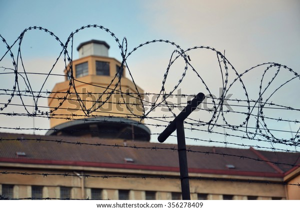 Barbed wire fence attached around prison walls