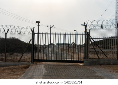 Barbed wire fence block the way. gate to a closed area. Automatic metal gate