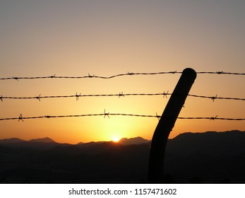 Barbed wire fence at dawn in Andalusian countryside