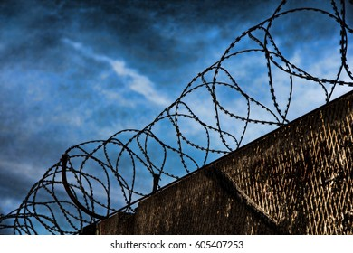 Barbed wire fence detail against of the night dramatic sky taken closeup.