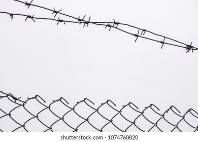 Barbed wire fence over dramatic gray sky