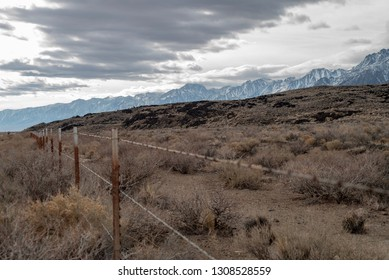 barbed wire fence through winter landscape with snowy mountains gray clouds